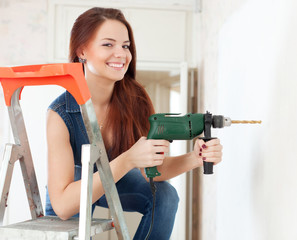 Happy woman drills hole in the wall