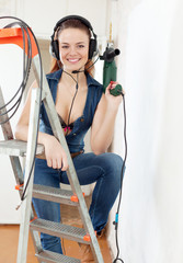 Portrait of sexy  girl in headphones with drill