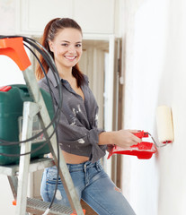 Happy girl  paints wall with roller at home
