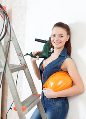 sexy  girl in headphones with drill and hardhat