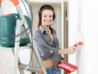 girl in headphones paints wall with roller
