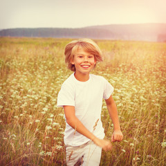 Happy boy running on summer field.