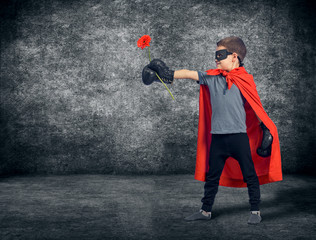 Superhero kid wearing boxing gloves and flower.