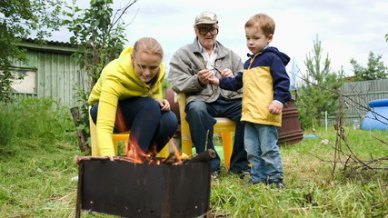 Mother, son and grandpa by the fire in the yard