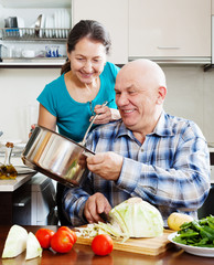 happy ordinary mature couple cooking together