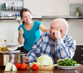 happy playing mature couple cooking food