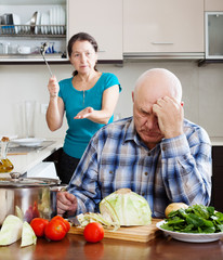 Senior couple after quarrel in kitchen at home