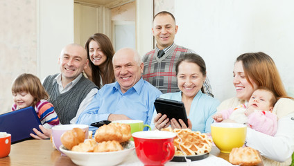 Happy family of three generations with electronic devices