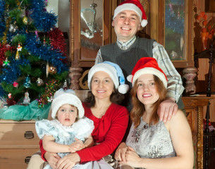 Happy family of three generations in Santa hats