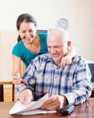 Joyful mature couple reading financial documents