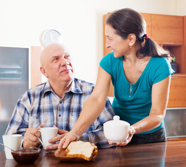 mature woman serving toast to  happy husband