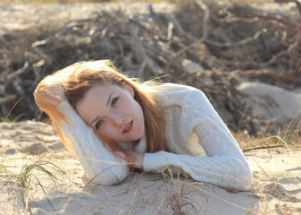 Beautiful young woman relaxing on the beach in the autumn