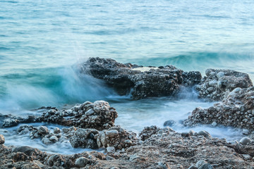 Rocks in the blue sea with small waves