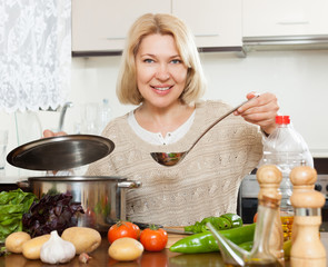 Beautiful mature woman cooking  soup