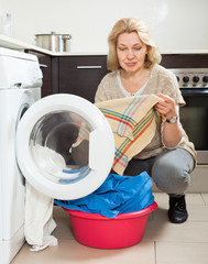 Home laundry. Unhappy  woman using washing machine