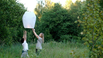 Family flying a fire lantern in the woods
