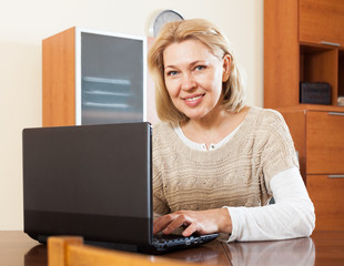 Portrait of a smiling  woman using laptop at home