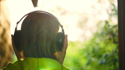 Girl listening to music in headphones outdoor