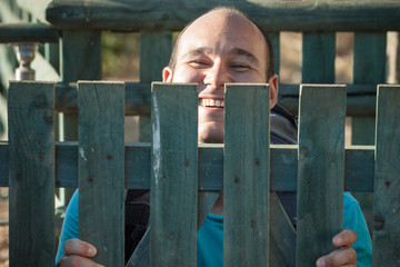 Happy man behind fence