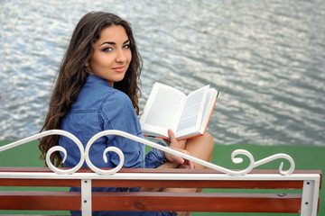 Brunette reading a book on a bench
