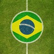 Football field center closeup with Brazilian flag in circle