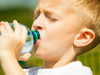 Little boy drink water from bottle, outdoor
