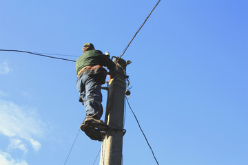 Electrician working on electric power pole