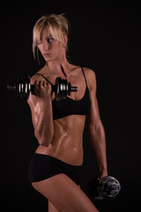 Athletic woman doing workout with weights on dark background