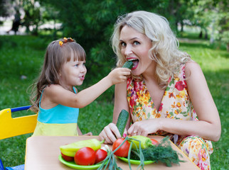 Girl daughter kid child feeding mother mum with cucumber outdoor