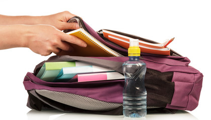 Hand with exercise book and bag