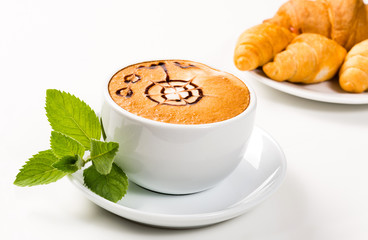large cup of coffee and croissants on a plate