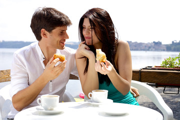 Couple in love having breakfast in front of lake in vacation