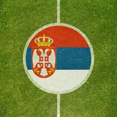 Football field center closeup with Serbian flag in circle