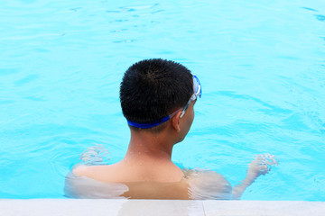 Young boy swimming in the pool.