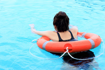 Girl swimming in the pool wearing life ring