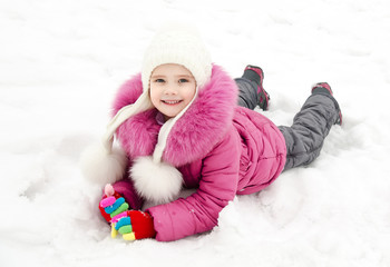 Cute smiling little girl lying on snow in winter day