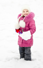 Portrait of smiling little girl with shovel in winter day
