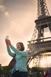 mature woman taking a selfie with the eiffel tower paris