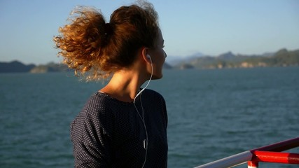 Young Woman Smiling and Listening Music in Headphones against