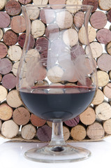 Glass of wine on a background of corks