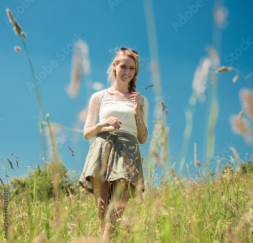 canvas print picture young woman in a summer grassland