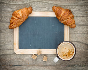 Coffee and croissant on a wooden board