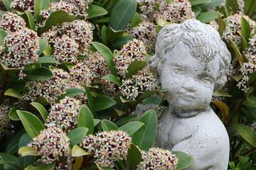 Junge aus Keramik inmitten von Blüten