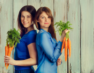 Young smiling women holds bunch of carrots
