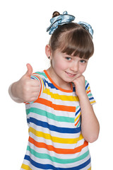 Shy little girl holds her thumbs up