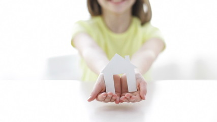 close-up of smiling girl holding paper house