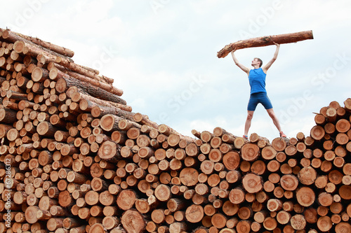 canvas print picture man on top of large pile of logs, lifting heavy log