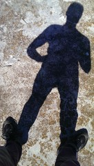 Male feet standing on concrete with shadow silhouette
