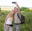 Happy couple taking selfie photo with smart phone hiking.
