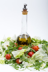 Heap of ruccola, lettuce,  tomatoes and olive oil with the thyme
